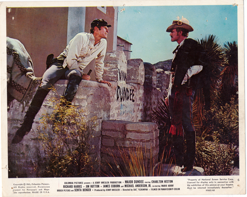Pictured is a US promotional 8x10 color lobby card from the 1965 Sam Peckinpah film Major Dundee starring Charlton Heston.