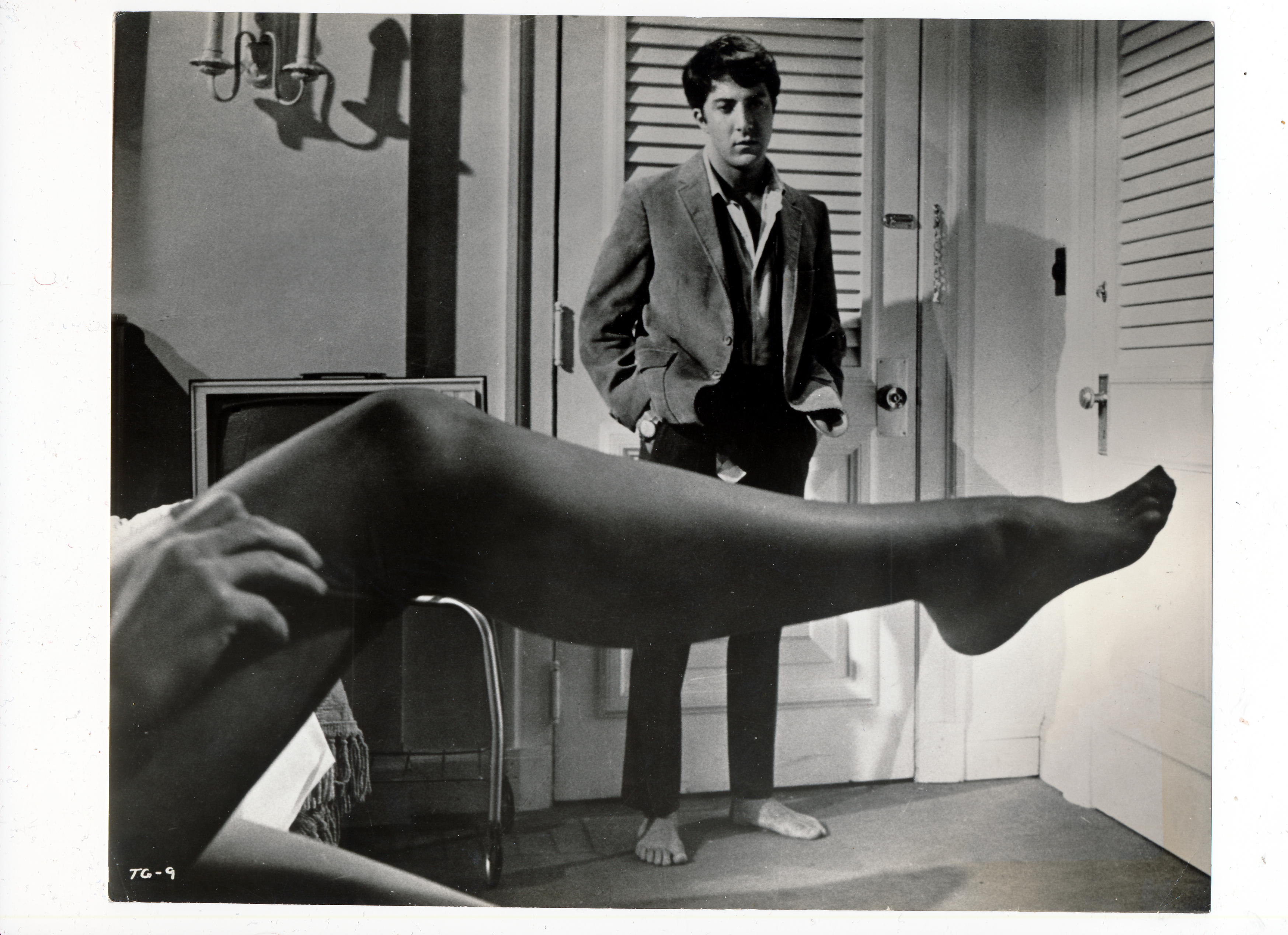 Pictured is a promostional black-and-white still from the 1967 Mike Nichols film The Graduate starraing Dustin Hoffman.
