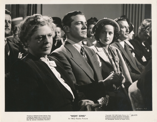 Pictured is a US promotional still photo from the 1947 John Cromwell film Night Song starring Dana Andrews and Merle Oberon.