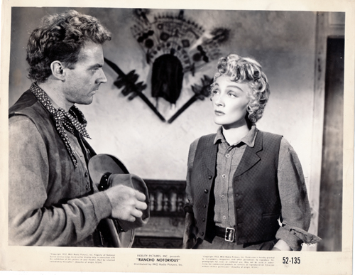 Pictured is a US promotional still photo from the 1952 Fritz Lang film Rancho Notorious starring Marlene Dietrich and Arthur Kennedy.