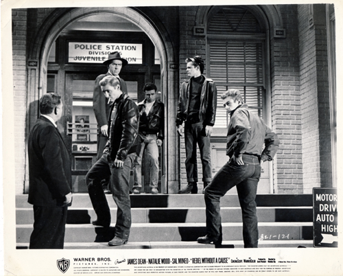 Pictured is a promotional black-and-white still for the 1955 Nicholas Ray film Rebel without a Cause starring James Dean and Natalie Wood.